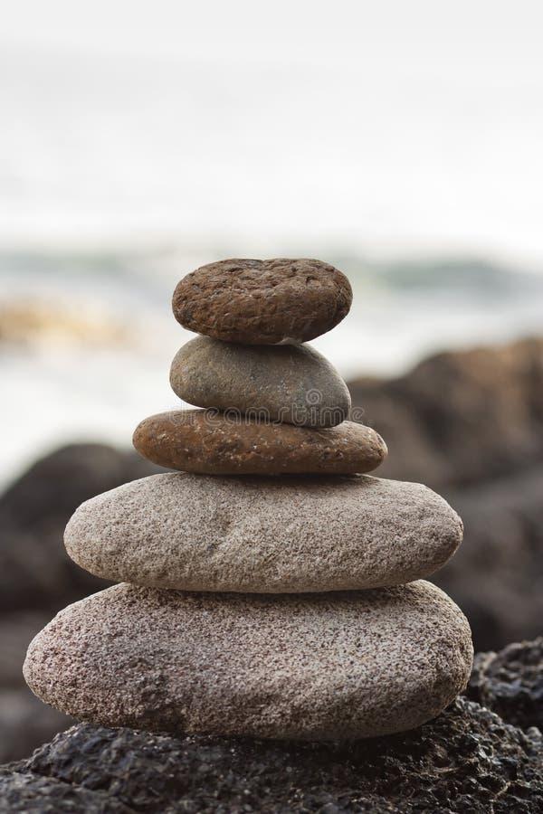 Stones pyramid on sand symbolizing zen, harmony, balance. Ocean in the background stock photos