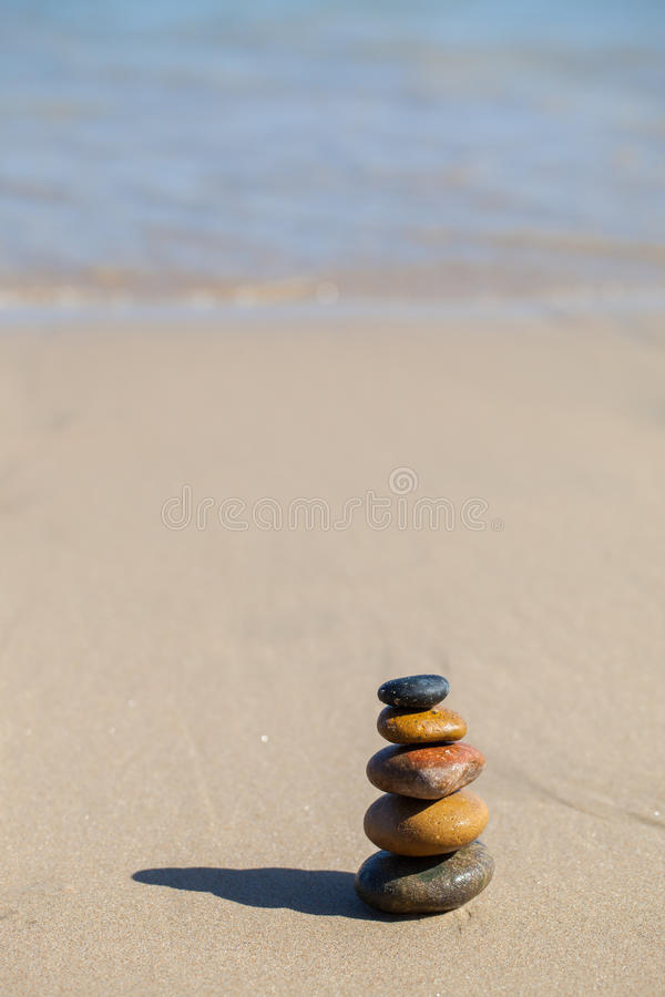 Stones pyramid on sandy beach. Symbolizing zen, harmony, balance royalty free stock photo