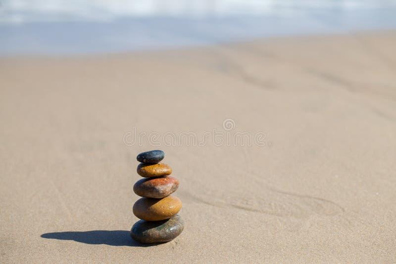 Stones pyramid on sandy beach. Symbolizing zen, harmony, balance royalty free stock image