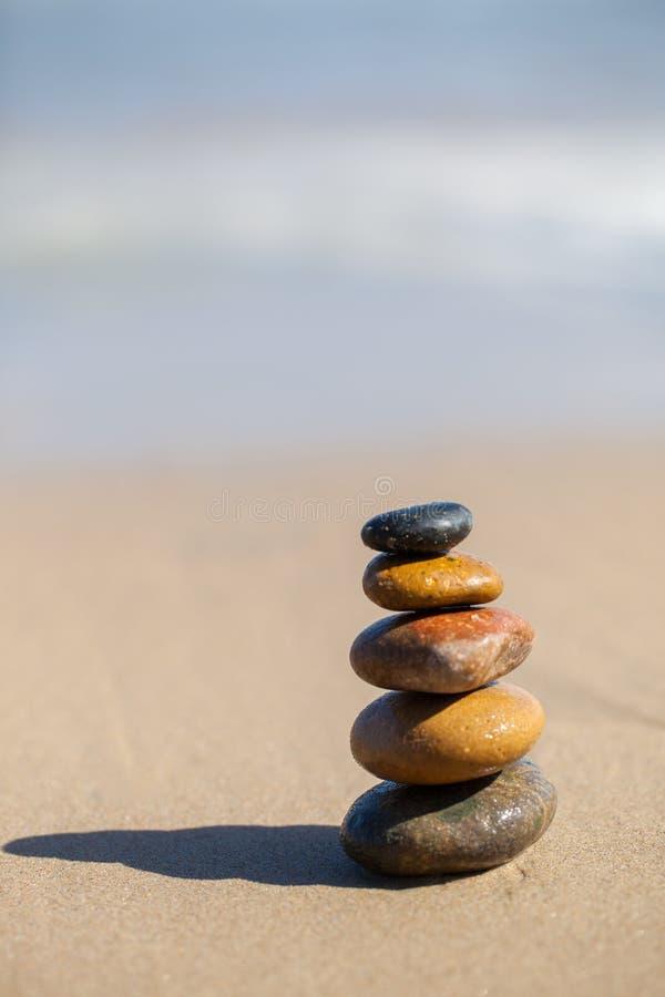 Stones pyramid on sandy beach. Symbolizing zen, harmony, balance stock photography