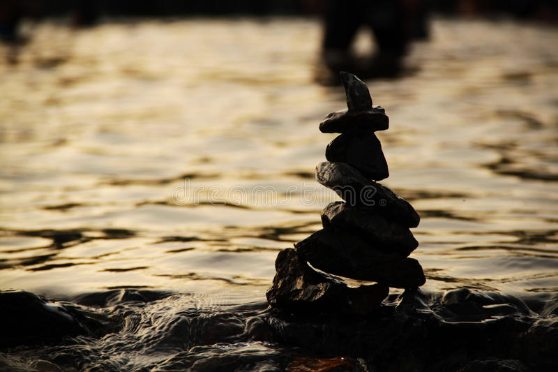 Stones pyramid on the water symbolizing zen, harmony, background. Stone symbol background silhouette abstract royalty free stock photography