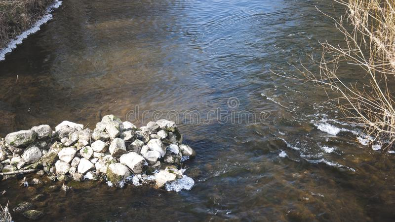 Stones in the river with little waves and vortex. And tree. There is pure water stock photo