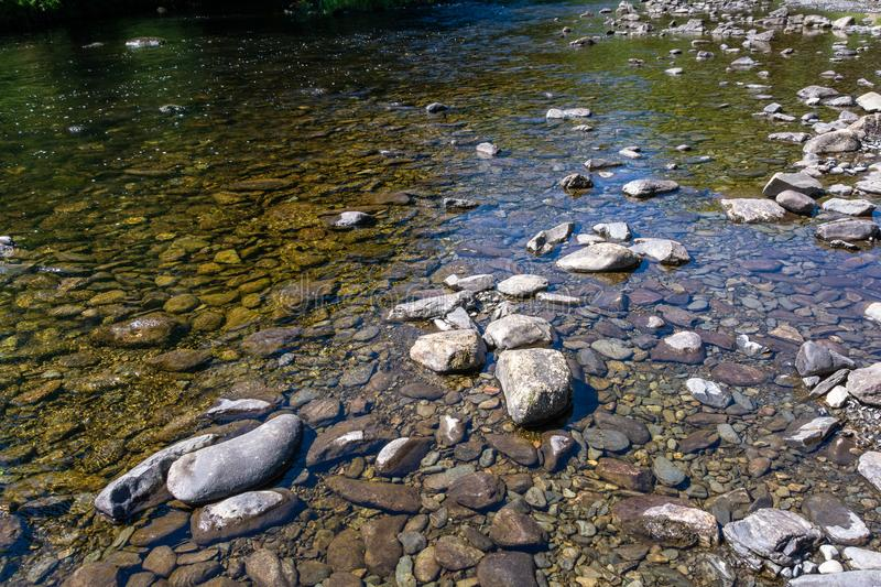 Stones and rocks on the bank of shallow stream. On midday royalty free stock images