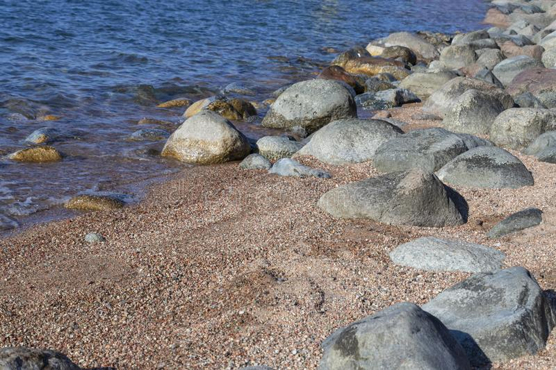 Stones and sand in clear water on the beach of a mountain lake Issyl-Kul royalty free stock images