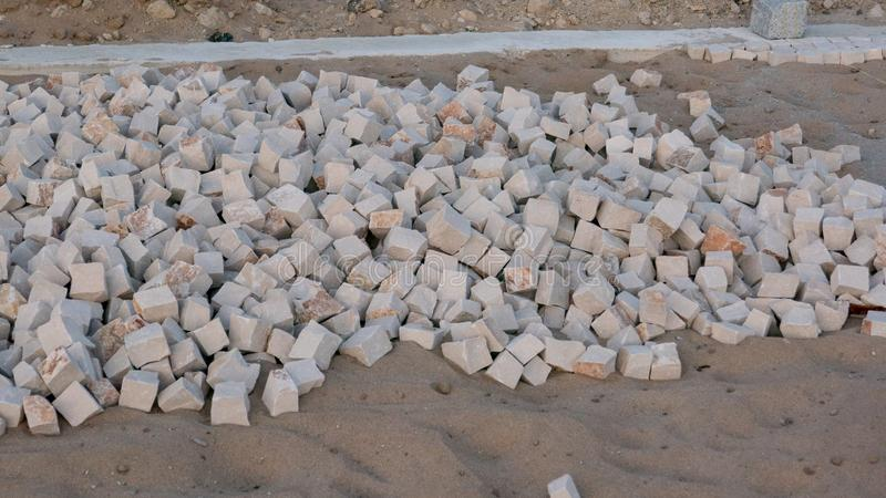 Stones in sand for construction of a Portuguese sidewalk / pavement in Portugal. Close up royalty free stock images