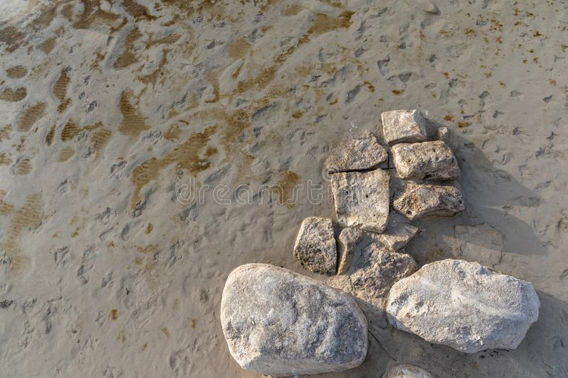 Stones on the sandy shore during the day.  stock photography