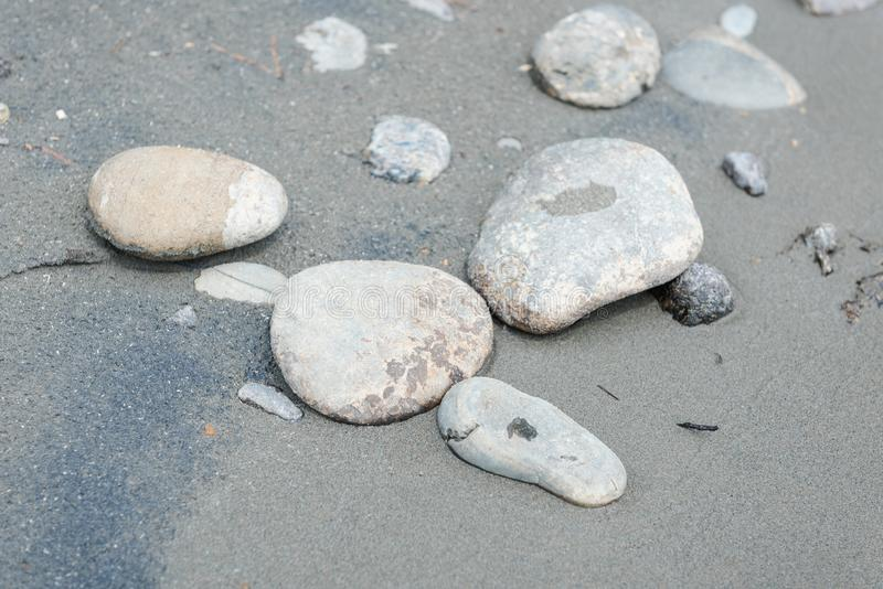 Stones on the sandy shore. Flat stones lie on the fine sand. The shore of a mountain river. Landscape in the Altai Mountains. Stones close-up. Fine gray sand stock image
