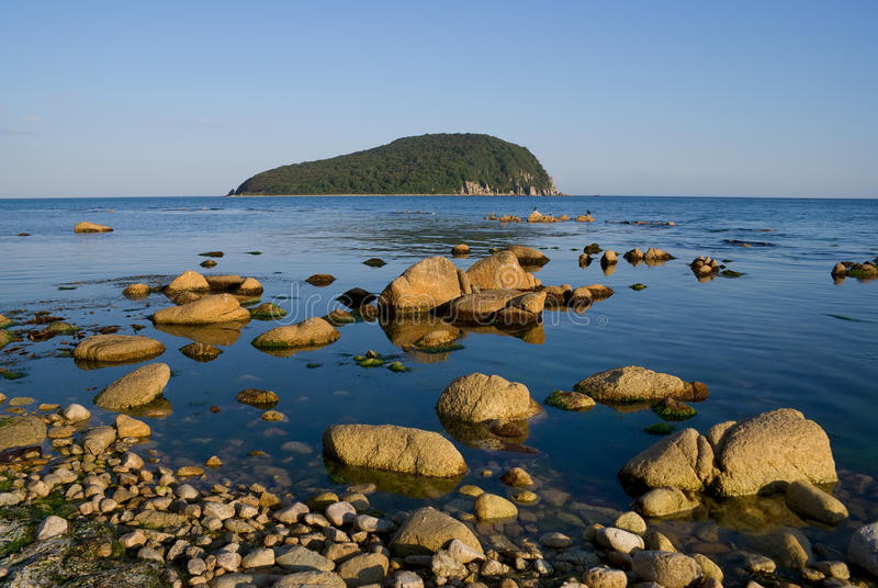 Stones and Sea 7. A close-up of the stones in sea. On background is green island. Russian Far East, Primorye, nature state reserve Lazovsky, Petrova island royalty free stock image