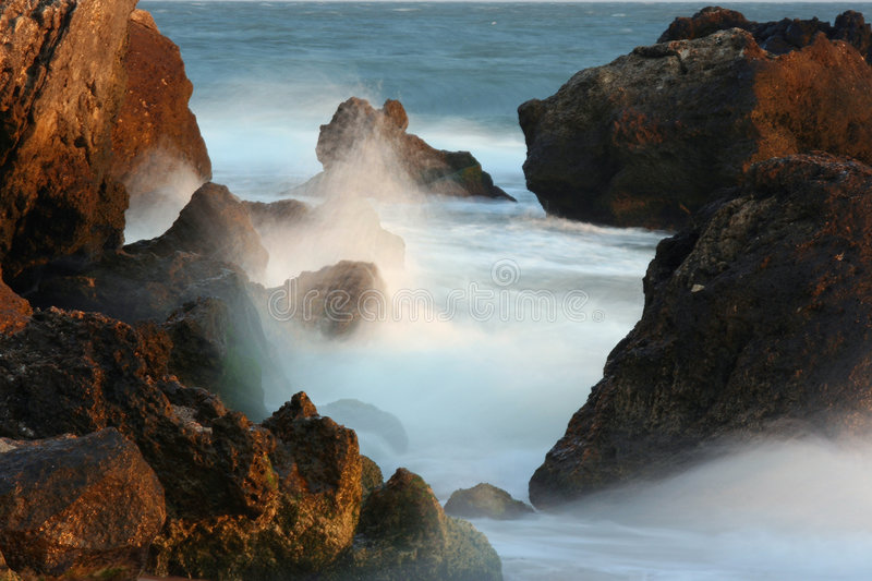 Stones and sea surf. Are shined by the morning sun royalty free stock photo