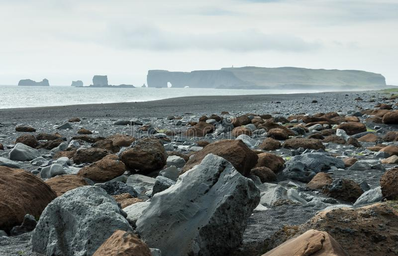 Shore of Reynisfjara Beach with Dyrholaey lighthouse in its background. Stones of the shore of Reynisfjara Beach with Dyrholaey lighthouse in its background royalty free stock image