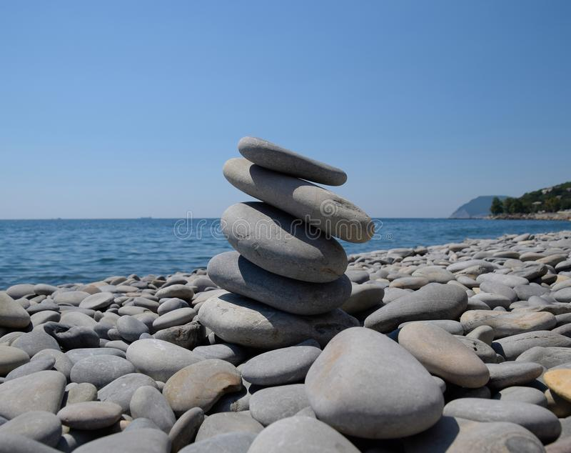 Stones stacked on top of each other against the background of the sea.  royalty free stock images