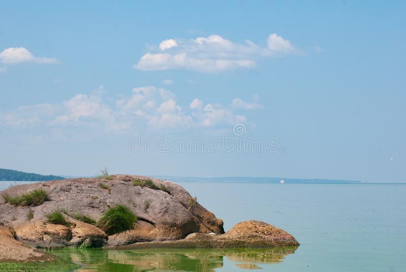 Stones in a stream with smooth running water, idealistic landscape, Sunny day on the river,. Rocks on the river royalty free stock image