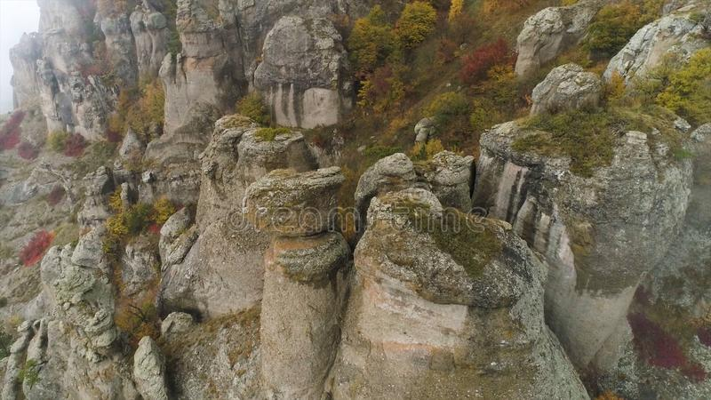 Stones of unusual forms on the mountain covered with fog clouds. Shot. Aerial view for foggy day in the mountains and royalty free stock images