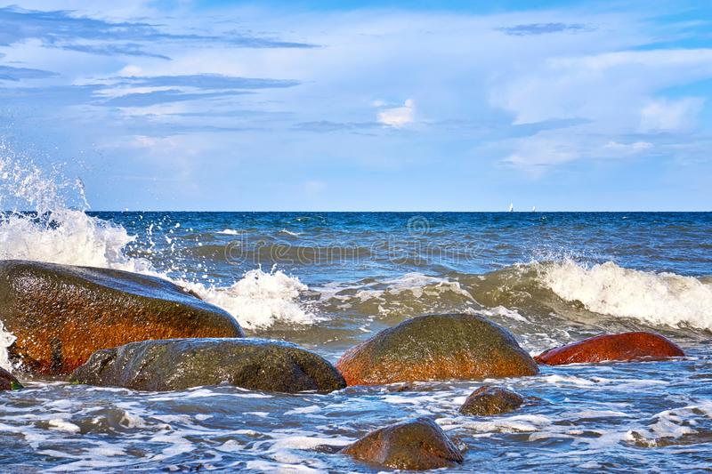 Stones and waves in the Baltic Sea with sailboats in the background. Horizon, sunlight, beautiful, beauty, foaming, blue, nature, outdoors, sand, sky, undulate royalty free stock photos