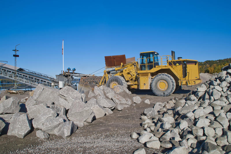Stones and wheel loader on brekke quarries. Brekke quarries is a company in Halden engaged in extraction of gravel, sand pits and mining of clays and kaolin stock photo