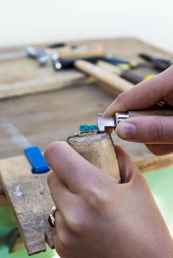 Stonesetting. A rough amazonite gemstone using a ring clamp and a burnishing tool stock photo