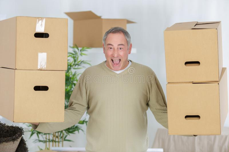 Stong mature man carrying boxes during moving stock photos