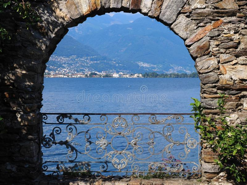 Stony arch at Brissago island in Switzerland with scenic alpine view on swiss Lake Maggiore royalty free stock photography