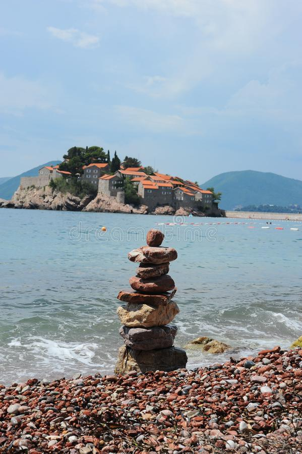 Stony beach, Adriatic Sea, Montenegro, Europe, the island of St. Stephen. Stony beach on the shore of the Adriatic Sea, against the blue sky, mountains, and stock image
