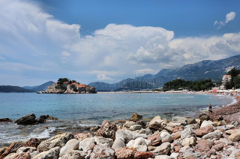 Stony beach, Adriatic Sea, Montenegro, Europe, the island of St. Stephen. Stony beach on the shore of the Adriatic Sea, against the blue sky, mountains, and stock images