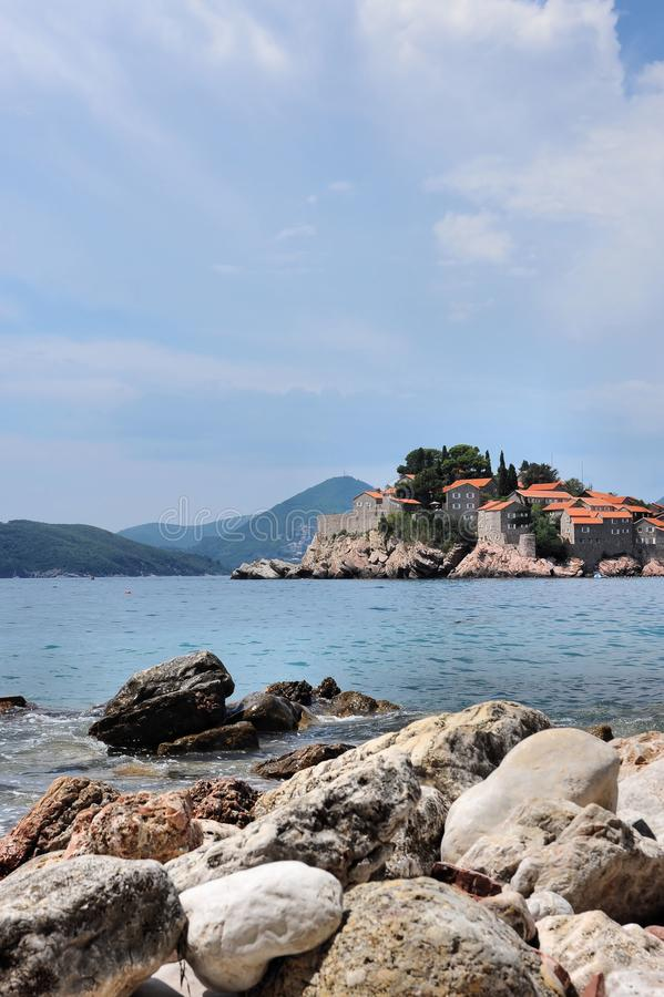 Stony beach, Adriatic Sea, Montenegro, Europe, the island of St. Stephen. Stony beach on the shore of the Adriatic Sea, against the blue sky, mountains, and royalty free stock photo