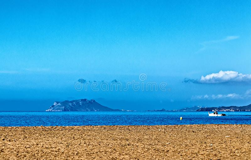 A stony beach looking out to an island royalty free stock photography