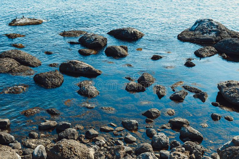 Stony beach. Rocky beach by the sea, spray, wave, stony, nature, summer, water, travel, landscape, outdoor, ocean, stone, splash, shore, coastline, foam, froth royalty free stock photography