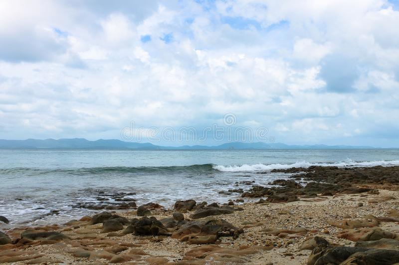 Stony beach, sea and mountains in the distance. Stony shore by the sea against the backdrop of the mountains stock photo