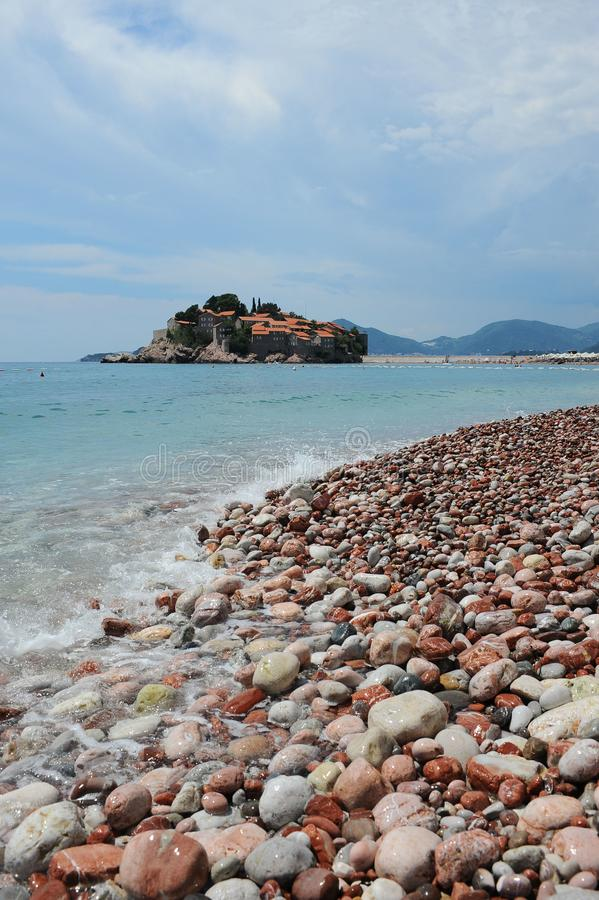 Stony beach, Adriatic Sea, Montenegro, Europe, the island of St. Stephen. Stony beach on the shore of the Adriatic Sea, against the blue sky, mountains, and royalty free stock photos