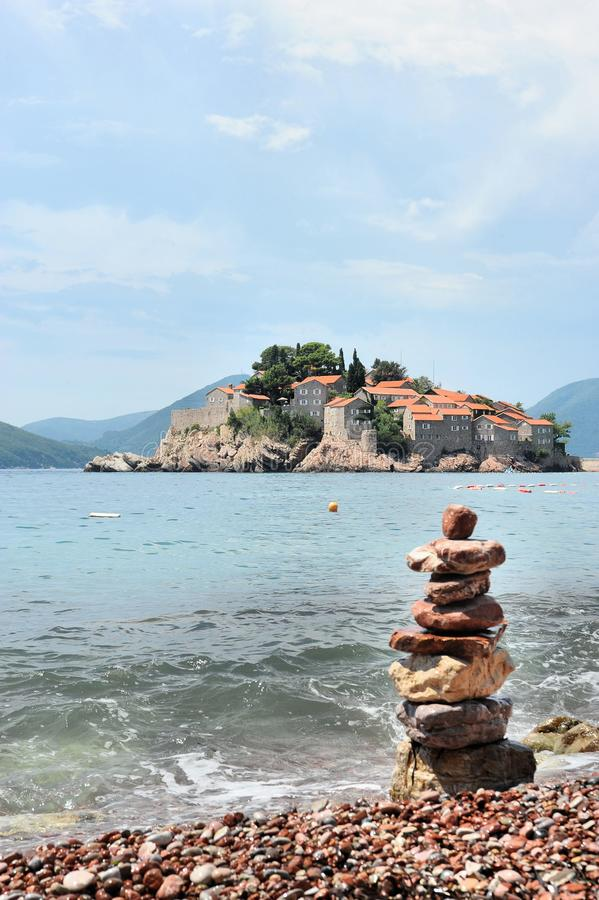 Stony beach, Adriatic Sea, Montenegro, Europe, the island of St. Stephen. Stony beach on the shore of the Adriatic Sea, against the blue sky, mountains, and stock photography