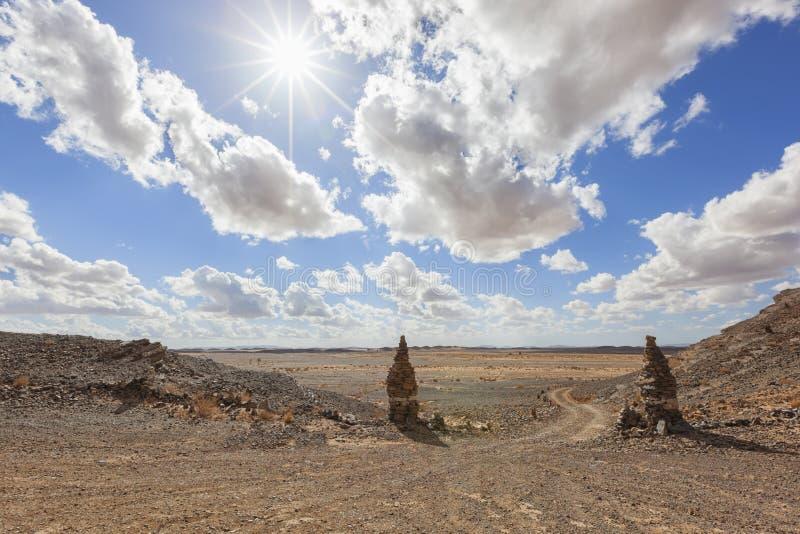 Stony desert landscape with cloudy blue sky.