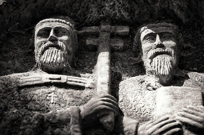 Stony figures of Saint Constantin and Method. With crucifix in sharp light royalty free stock photo