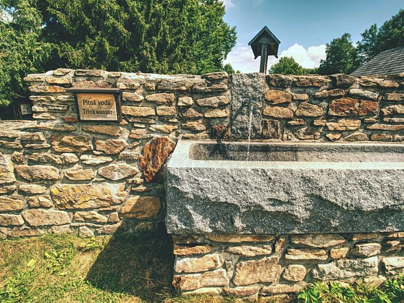 Stony fountain in nature with iron faucet.  Natural resources. Ancient stony fountain in nature with iron faucet.  Natural resources, water source concept, tap royalty free stock photo