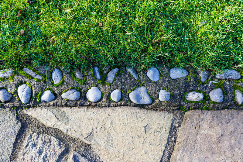 Stony and green grass pathway texture. Close up photo of stony and green grass pathway texture stock images
