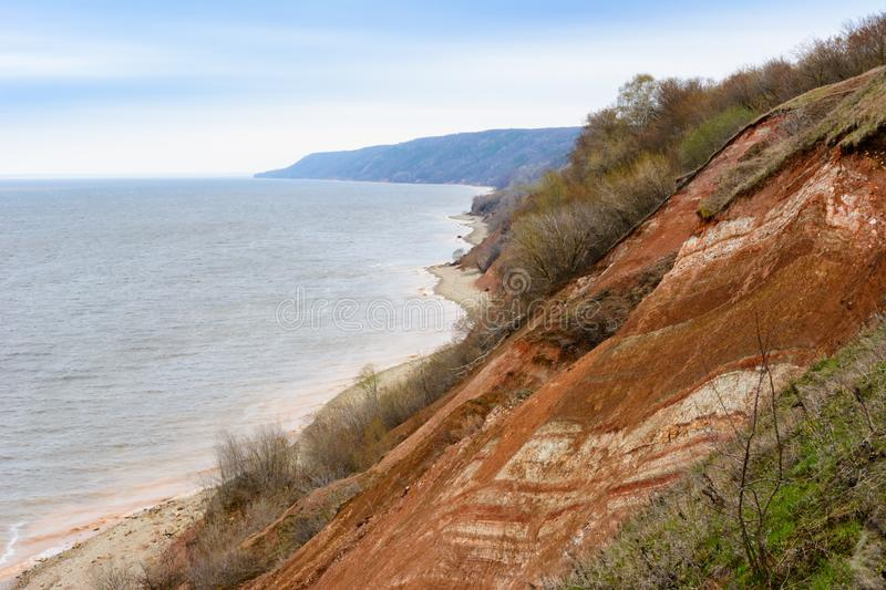 Stony, pebble and clay banks of the Volga River. Mountain slope of various stone rocks. Spring cloudy day with rain. Beautiful stock photo
