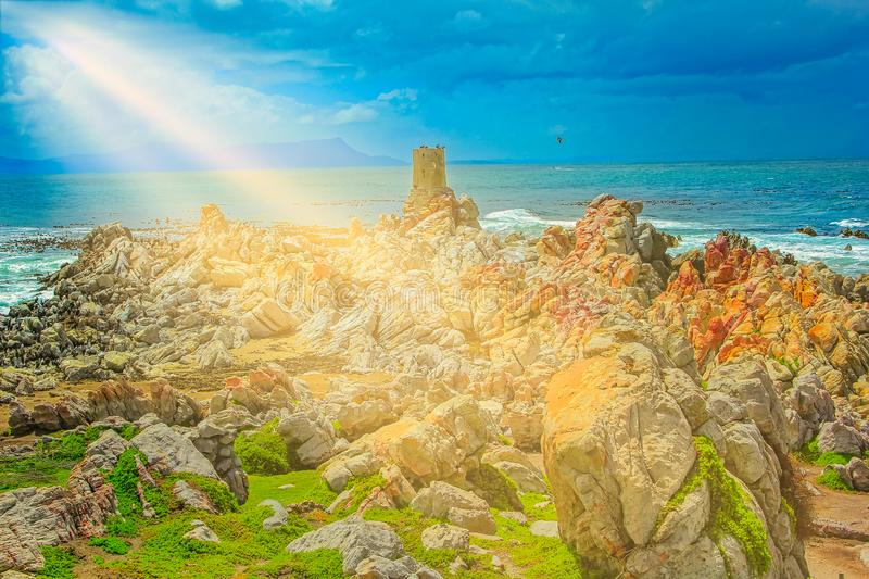 Stony Point sunbeams. Sun shining on the old whale watching tower at Stony Point, one of the largest breeding colonies of African Penguin, near Betty`s Bay royalty free stock photo