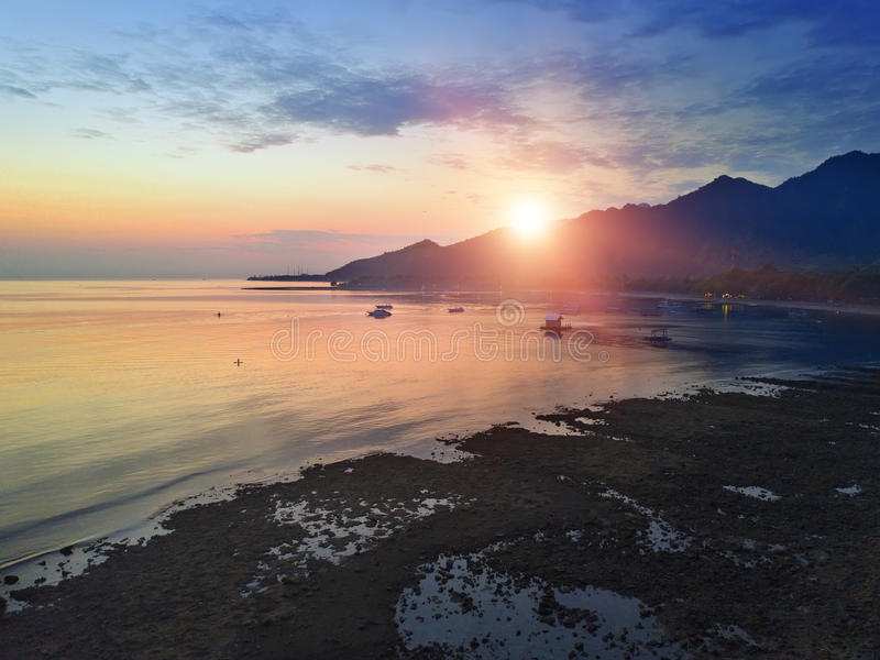 Stony seacoast and mountains on a sunset. Indonesia. Bali stock image