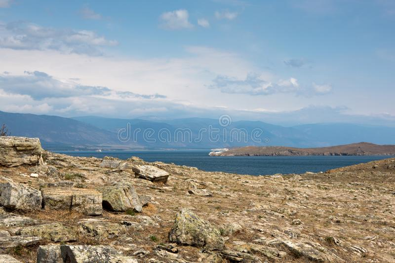 Stony seashore. Summer sunny day. Stones in the foreground. Blue-brown colors royalty free stock image