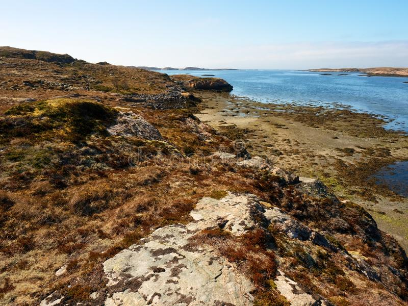 Stony shore of the North sea. First warm spring day, poor dry grass on rocky hillside. At cold blue ocean royalty free stock photos