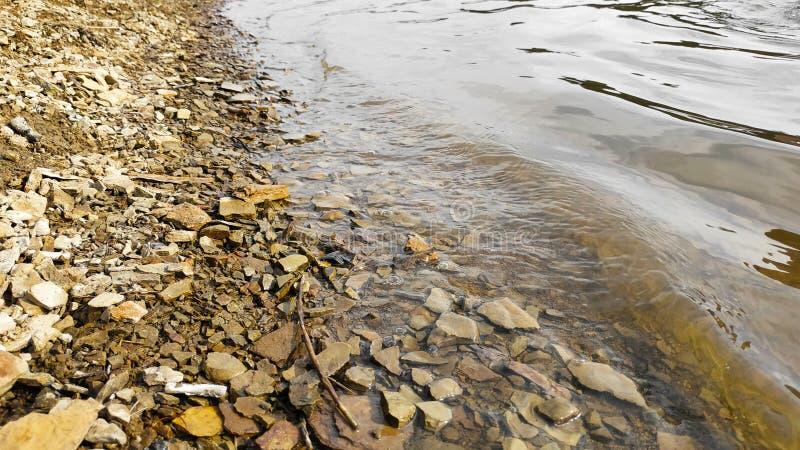 Stony shore of the reservoir. River beach royalty free stock photo