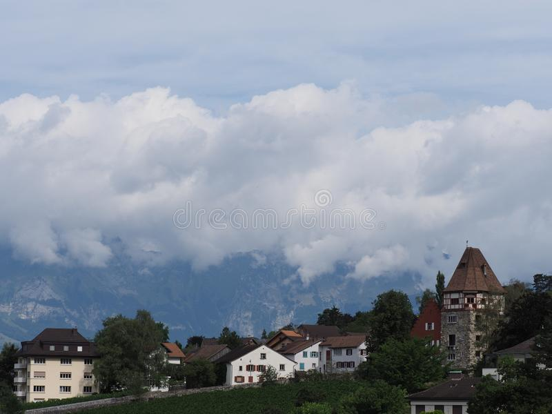Tower and scenic housing estate on hill at cityscape landscape of clouds above european capital Vaduz city Liechtenstein royalty free stock image