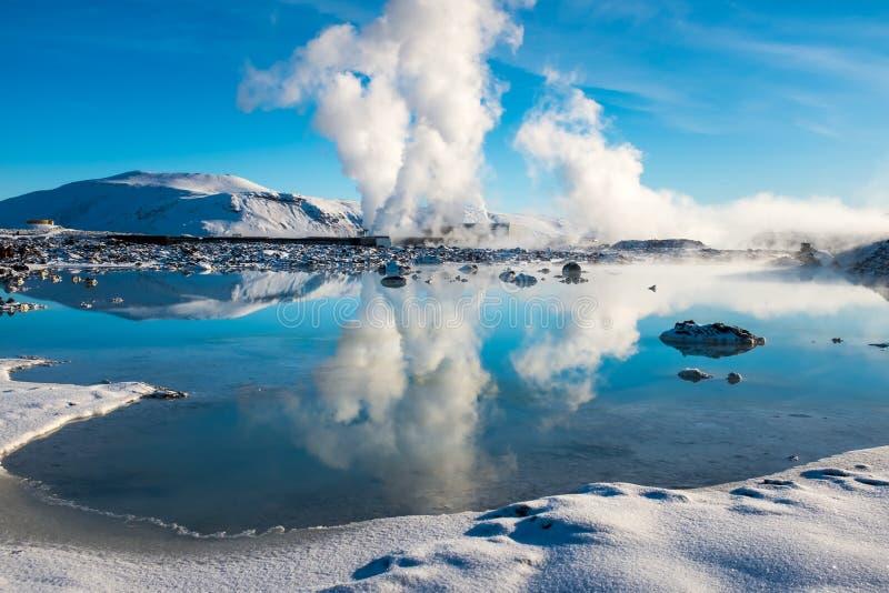 Stoom van een geothermische installatie die tegen een heldere blauwe hemel wordt geplaatst en die in een meer naast de Blauwe Lag royalty-vrije stock foto