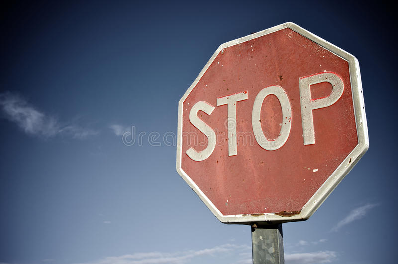 Stop. Old and damaged stop sign against a blue sky stock images