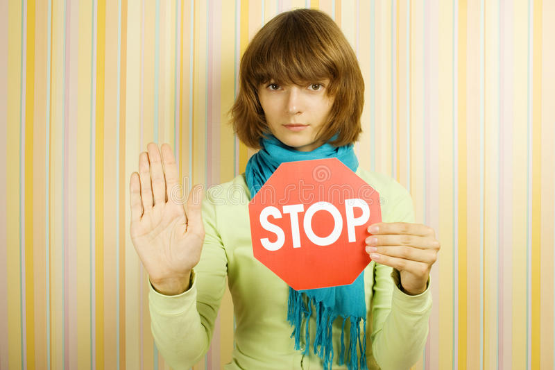 STOP. Young woman in the room holding STOP sign stock photography
