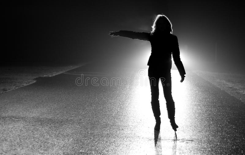 Stop!. Woman - hitchhikers silhouette at night in car highlights stopping a car royalty free stock image