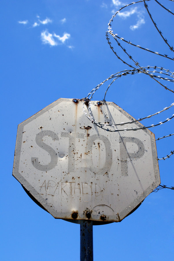 Stop Apartheid. An old STOP road sign, with the words APARTHEID added by an unknown apartheid victim. This photo also includes barbed wire, used to control stock photography