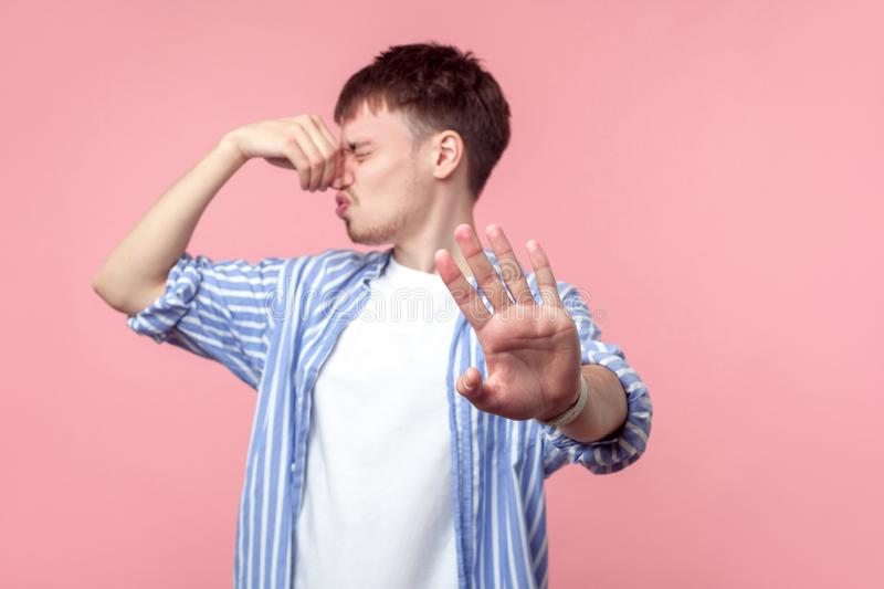 Stop this bad smell! Portrait of annoyed displeased brown-haired man with small beard in casual shirt pinching his nose. isolated. Stop this bad smell! Portrait royalty free stock image