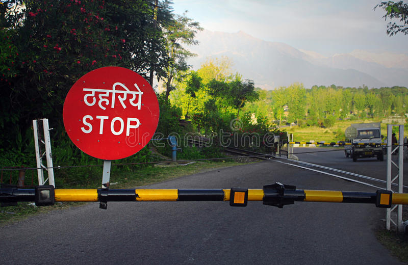 Stop barricade on railroad crossing, India. Railroad Crossing-Xing Stop barrier near en route to scenic Himalayan mountains in Kangra district, state of Himachal stock photo