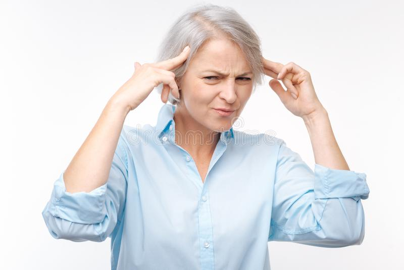 Irritated grey-haired woman pressing fingers to temples stock photography