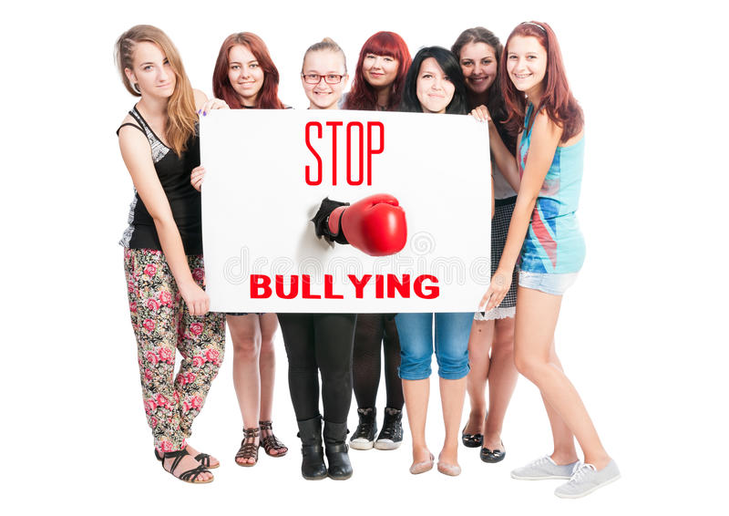 Stop Bullying. Concept text on white cardboard help by teen girls royalty free stock image